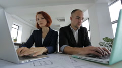 Businesswoman and Businessman in suits sitting in a large bright spacious office - stock footage