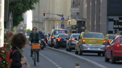 Riding bike and driving cars on a street in Bucharest Stock Footage