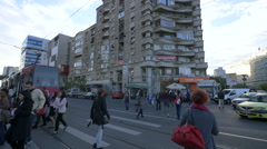 People crossing the street near a tram station in Bucharest Stock Footage