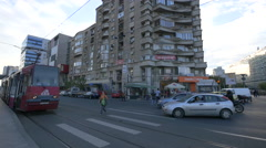 Driving cars near a tram stopped in the tram station in Bucharest Stock Footage