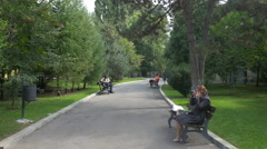 People sitting on benches in a small park in Bucharest Stock Footage