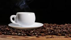 Cup with hot drink on roasted coffee beans Stock Footage