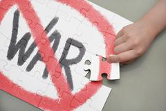 """Child's hand adds puzzle with """"Stop war"""" drawing Stock Photos"""