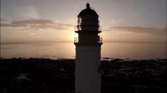Aerial shot of a lighthouse during a beautiful sunrise in Scotland Stock Footage