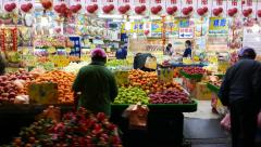 Fruits shop stalls put out at night street, fresh fruits on trays, people choose Stock Footage