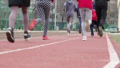 Children and sport young students running around the track a group of outside - stock footage