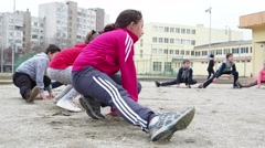 Children and sport students doing stretching squatting on feet - stock footage