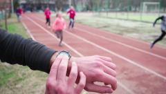 Children's sports training coach with a stopwatch on hand looking lap time Stock Footage
