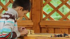 Boy puts chess on chessboard Stock Footage
