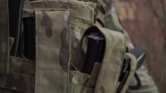Soldier puts assault rifle ammo into pockets of his ammo vest. Close up shot Stock Footage