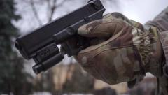 Soldier gets an automatic pistol out of the holster - stock footage