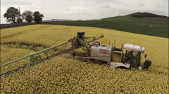 Aerial shot of a tractor in field spraying rapeseed revealing shot Stock Footage