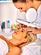Woman middle-aged in spa salon with cosmetic lamp - stock photo