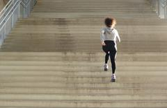 Young female athlete running up stairs - stock photo