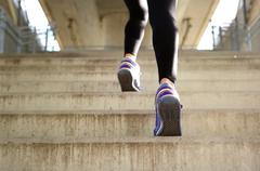 Sports female running up stairs - stock photo