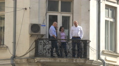 Three people standing on a balcony and talking in Bucharest Stock Footage