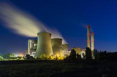 A large coal-fired power plant at night with a lot of steam and deep blue sky Stock Photos