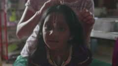 Young mother making hair of adopted Indian Girl Stock Footage