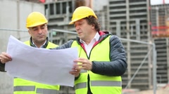 Construction site manager explaining office blueprints - stock footage