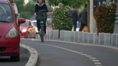 Two people riding bikes on a street in Bucharest Stock Footage