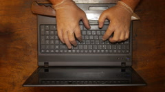 Stock Video Footage of Crook thieve spy hacker criminal terrorist with latex gloves and knife in laptop