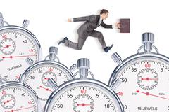 Businessman running with set of timers - stock photo