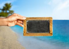 blackboard with advertising space  in background the beach with a blue sky - stock photo