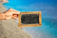 Blank blackboard with sea  in background - stock photo