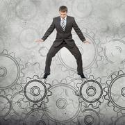 Businessman standing on cog wheels - stock photo