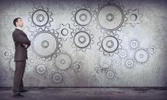 Businessman with cog wheels - stock photo