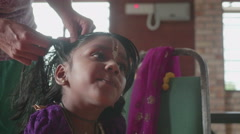 Young Indian GIrl habing hair done by her adoption mother - stock footage