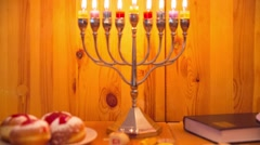 Jewish Holiday Hanukkah with menorah, donuts and wooden dreidels - Zoom Out Stock Footage