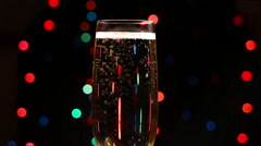 Bubbles inside a glass of champagne against the background of holiday lights Stock Footage