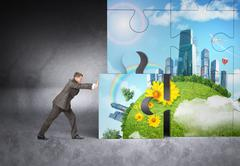 Man pushing puzzle piece of city picture Stock Photos