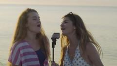 Teen Girls Sing And Dance On Beach, Pretend Gopro Stick Is A Microphone - stock footage