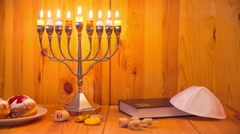 Jewish Holiday Hanukkah with menorah, donuts and wooden dreidels - Track Right Stock Footage
