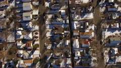 Aerial drone fly directly over snow covered winter houses to highway. Stock Footage