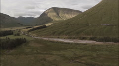 Aerial shot of a train going through the Scottish highlands Stock Footage