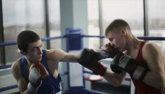 Two young professional boxers are fighting on the boxing ring. Slow motion - stock footage