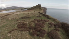 Cinematic aerial shot looking over the edge of a cliff on Skye in Scotland Stock Footage