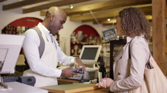 4K Woman uses a mobile phone to make contact-less payment in a wine shop - stock footage