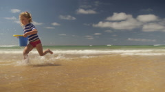 Little girl running with a bucket on the beach Stock Footage