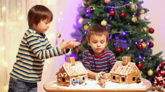 Two sweet boys, brothers, making gingerbread cookies house, decorating at hom Stock Footage