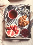 Cup of fresh tea and croissants into service tray on the bed - stock photo