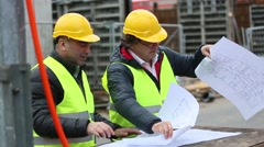 Architects checking office blueprints pointing at something on construction site - stock footage