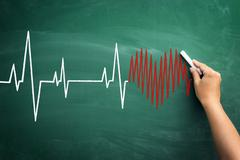 hand drawing heart and cardiogram on chalkboard - stock photo