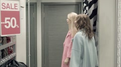 Two girls try on a coat in a locker room Stock Footage
