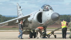 Ground crew checks a Harrier jumpjet during an airshow Stock Footage