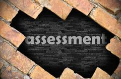 Hole in the brick wall with word assessment - stock photo