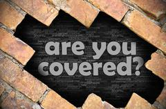 Hole in the brick wall with word are you covered? - stock photo